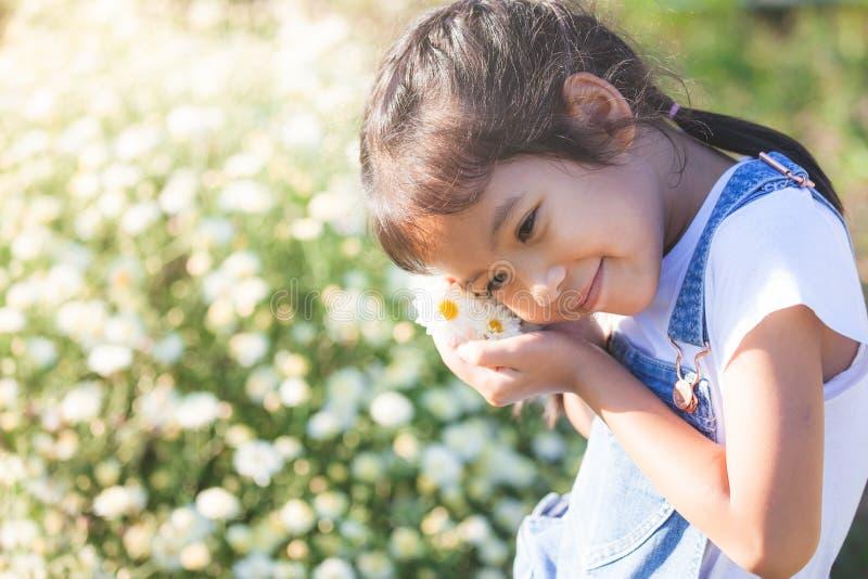 Gullig asiatisk barnflicka som ler och rymmer den lilla blomman i hand arkivfoto