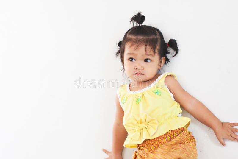 Gullig asiatisk flicka för litet barn i thailändskt traditionsklänninganseende i huset arkivfoton