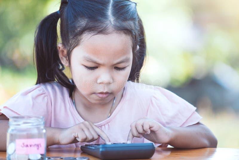 Gullig asiatisk flicka för litet barn som använder räknemaskinen royaltyfri fotografi