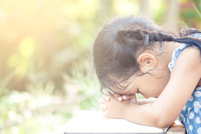 Gullig asiatisk flicka för litet barn som ber med vikt hennes hand royaltyfria foton