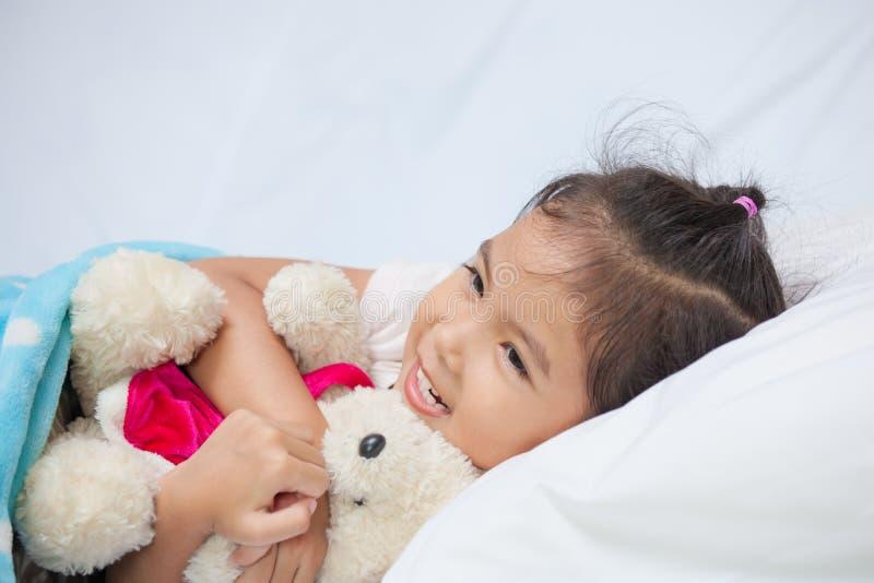 Gullig asiatisk flicka för litet barn som kramar hennes nallebjörn royaltyfria bilder
