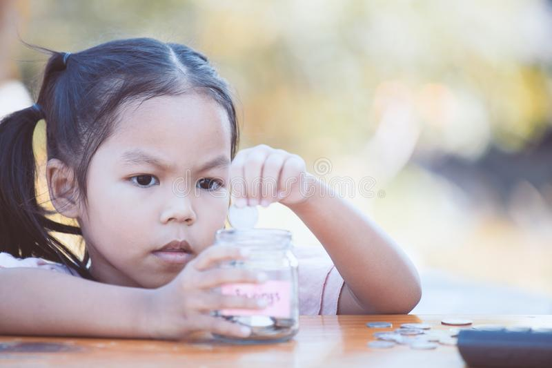 Gullig asiatisk flicka för litet barn som sätter myntet in i glasflaskan arkivfoton
