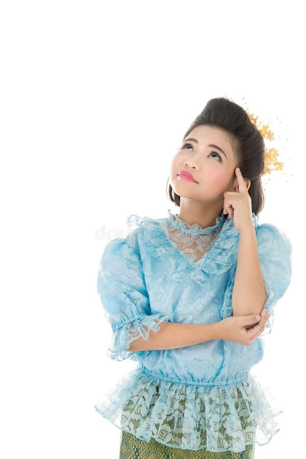 Gullig asiatisk flicka i thailändsk dräkt på vit bakgrund royaltyfria foton