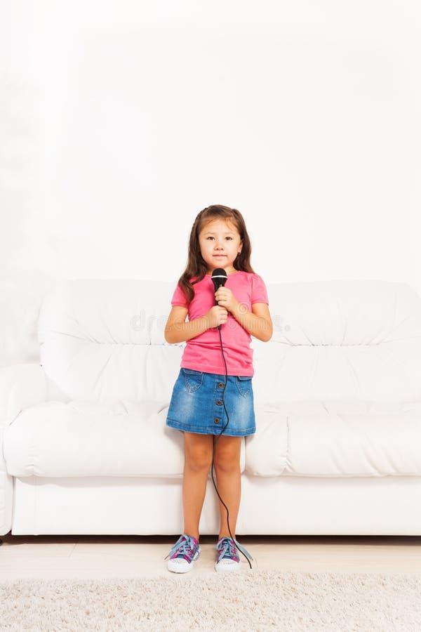 Gullig asiatisk flicka med mikrofonen arkivbilder