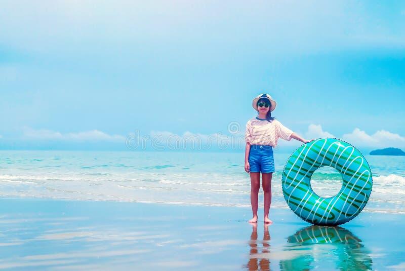 Gullig asiatisk flicka på cirkeln för bad för innehav för sommarhavsstrand, den bärande hatten, glasögon och att le med lycka, fo fotografering för bildbyråer