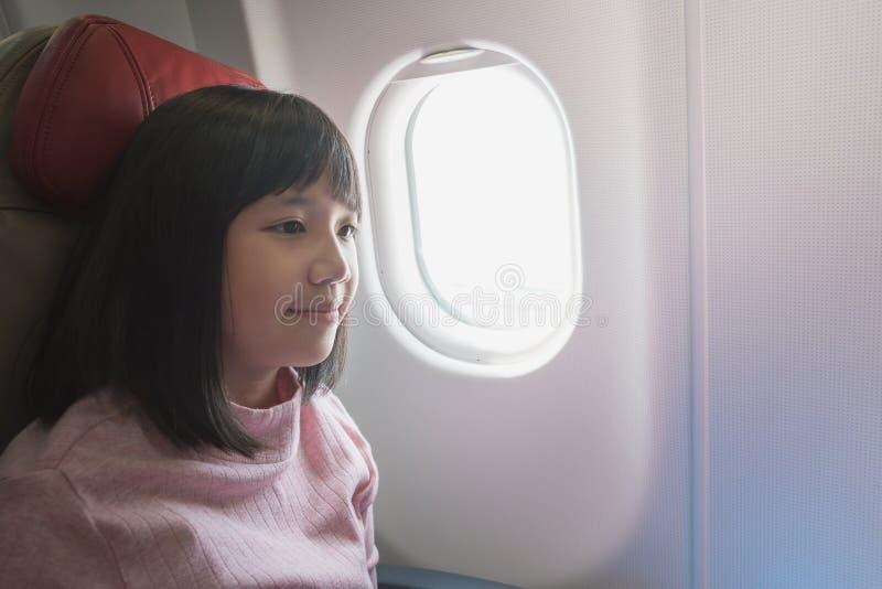 Gullig asiatisk flicka på flygplanet arkivbild