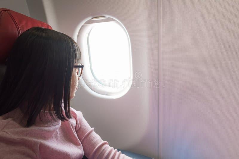 Gullig asiatisk flicka på flygplanet fotografering för bildbyråer