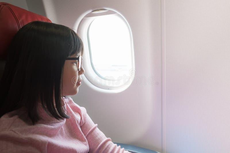Gullig asiatisk flicka på flygplanet royaltyfri bild