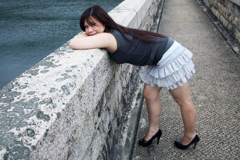 Gullig asiatisk flicka som över böjer arkivbild