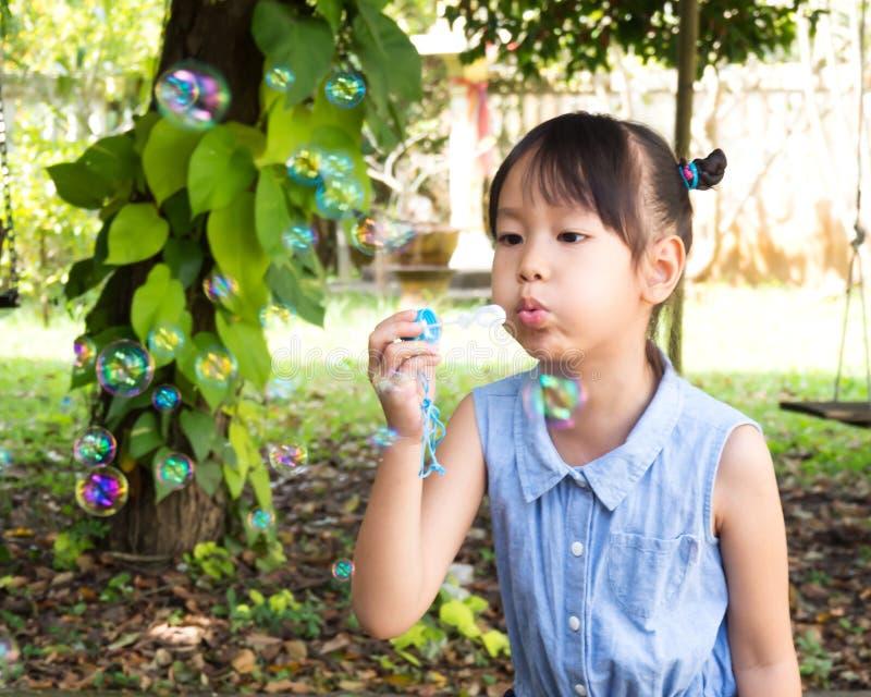 Gullig asiatisk flicka som blåser bubblan med trädgårds- sikt Rörelseskytte arkivbild