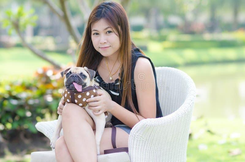 Gullig asiatisk flickakram som kopplar av på parkera med valpmopshunden royaltyfria bilder