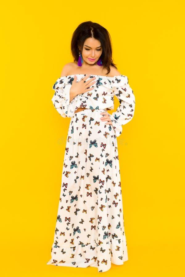 Gullig asiatisk kvinna i siden- klänning med fjärilar som poserar på gul bakgrund royaltyfri bild
