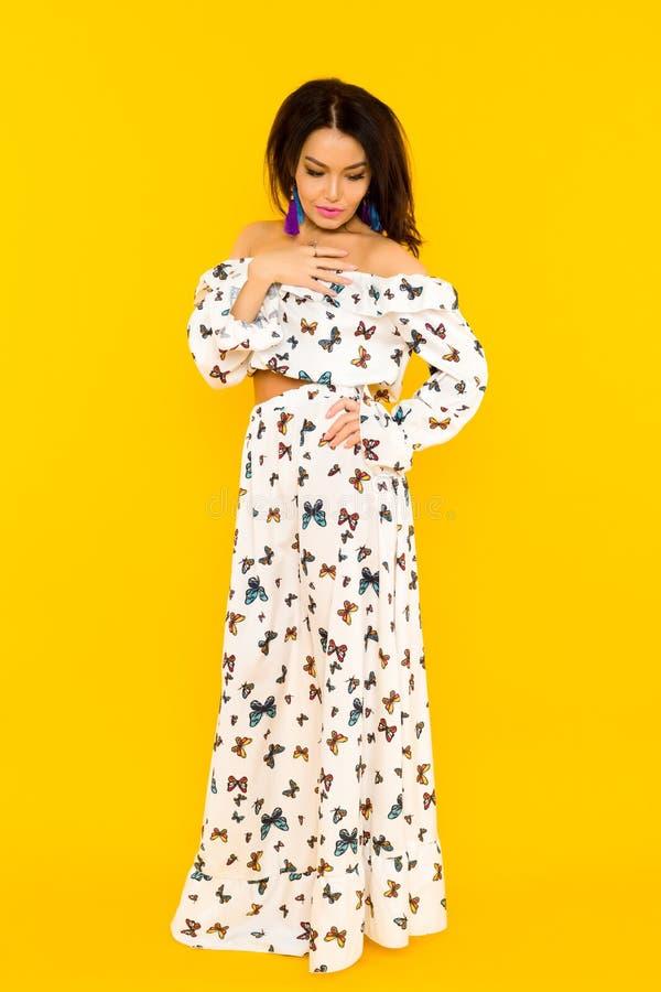 Gullig asiatisk kvinna i siden- klänning med fjärilar som poserar på gul bakgrund fotografering för bildbyråer