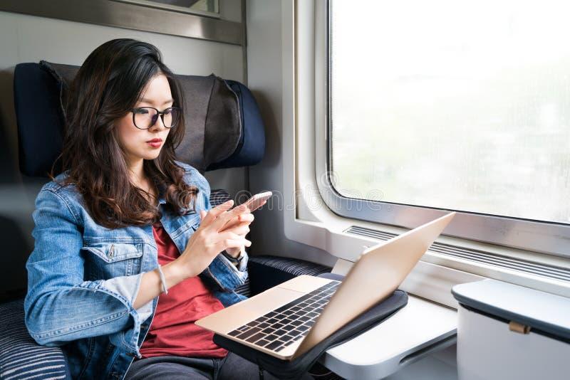 Gullig asiatisk kvinna som använder smartphonen och bärbara datorn på drevet, kopieringsutrymme på fönster, affärslopp eller tekn arkivbilder
