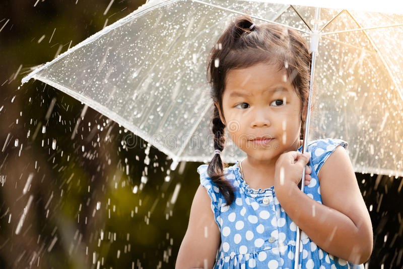 gullig asiatisk liten flicka med paraplyet i regn royaltyfria bilder