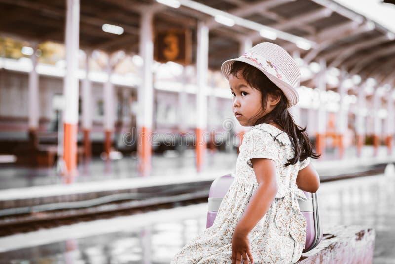 Gullig asiatisk liten flicka som väntar på drevet med resväskan arkivfoto