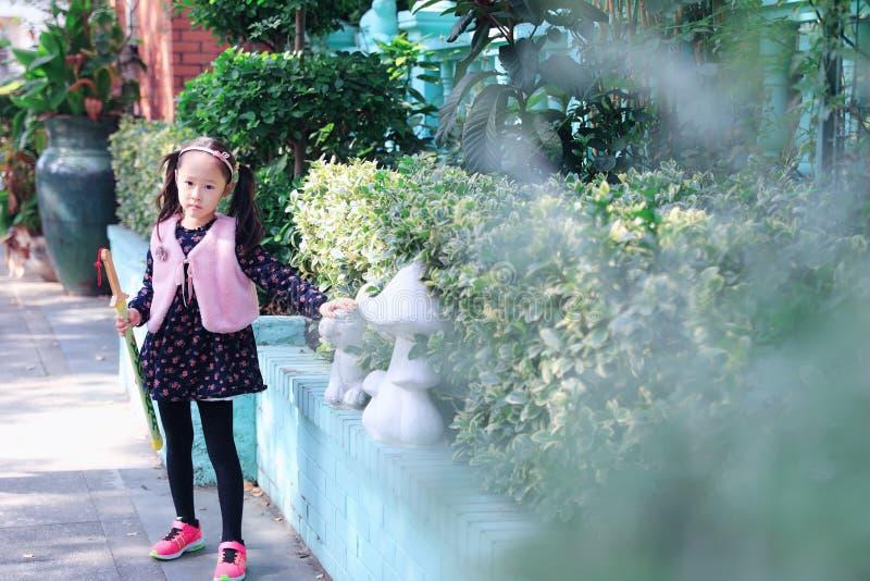 Gullig asiatisk liten härlig flickalek på hösten i staden parkerar royaltyfri fotografi