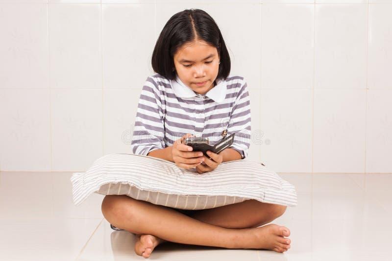 Gullig asiatisk mobil för flickasammanträdelek fotografering för bildbyråer