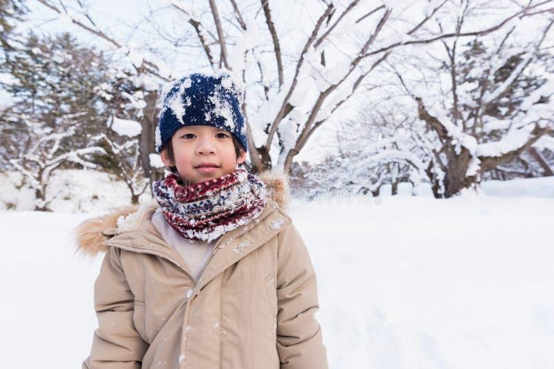 Gullig asiatisk pojke i vinter royaltyfri fotografi