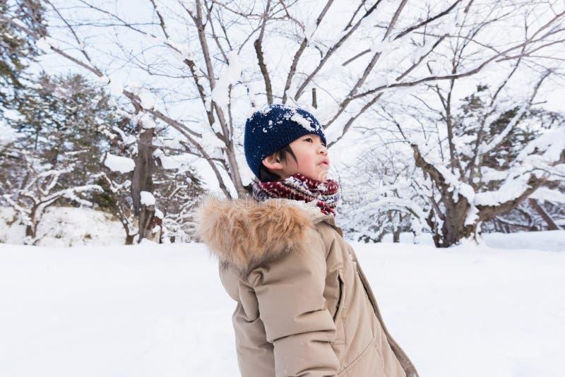 Gullig asiatisk pojke i vinter fotografering för bildbyråer
