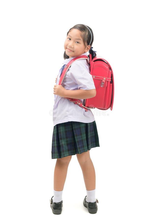 Gullig asiatisk student med den isolerade skolapåsen fotografering för bildbyråer