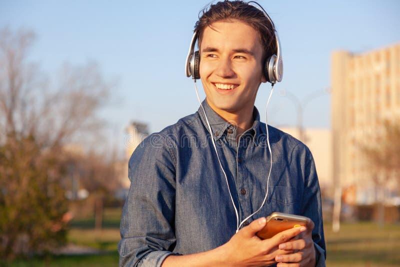Gullig asiatisk ton?rig pojke som lyssnar till musik p? h?rlurar i hans telefon som ler tycka om sikten royaltyfri foto