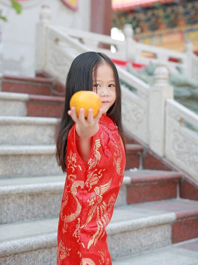 Gullig asiatisk ungeflicka i traditionell kinesisk klänning med den sakrala apelsinen för innehav på den kinesiska templet i bang arkivbilder