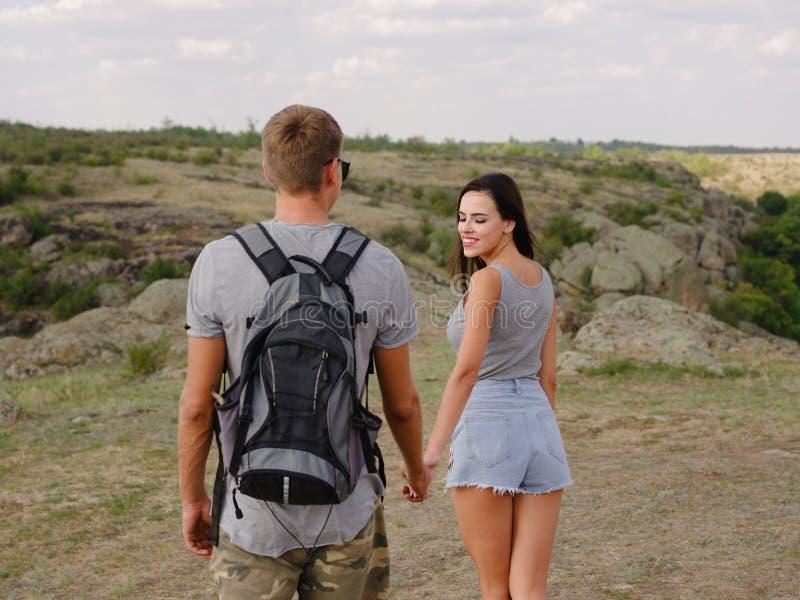 Gullig attraktiv flickvän och stark positiv pojkvän på en naturlig bakgrund Unga fotvandrare Romantiker snubblar begrepp royaltyfria bilder