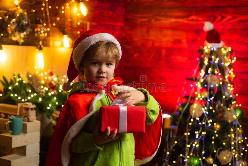 Gullig barnöppning per julklapp Gladlynt pys som kläs som Santa Claus En pojke i jultomtenhatt hjälper med fotografering för bildbyråer