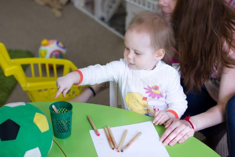 Gullig barnflicka i förträningen på tabellen i dagis dotterteckningsmoder tillsammans royaltyfri bild
