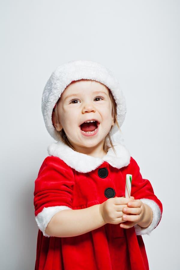 Gullig barnflicka i jultomtenhatten som har gyckel och att skratta royaltyfri foto