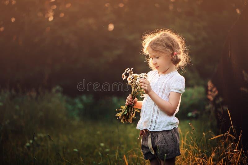 Gullig barnflicka med lösa blommor på sommarsolnedgångfält royaltyfri bild