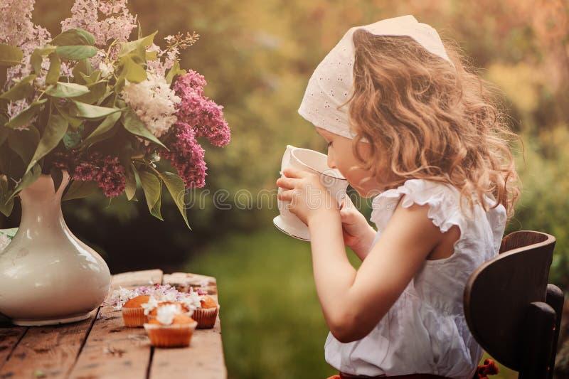 Gullig barnflicka på den hemtrevliga utomhus- tebjudningen i vårträdgård med buketten av lilor arkivfoton