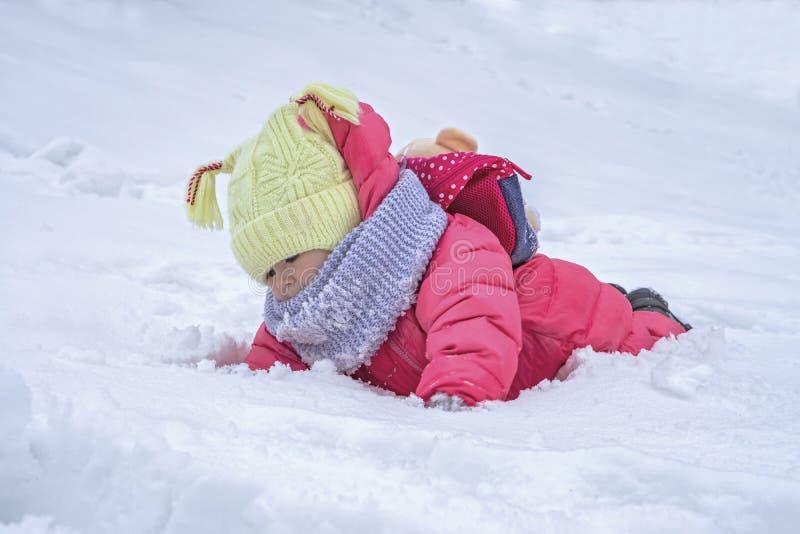 Gullig barnflicka på snö Utomhus- aktiviteter för vinter royaltyfri foto