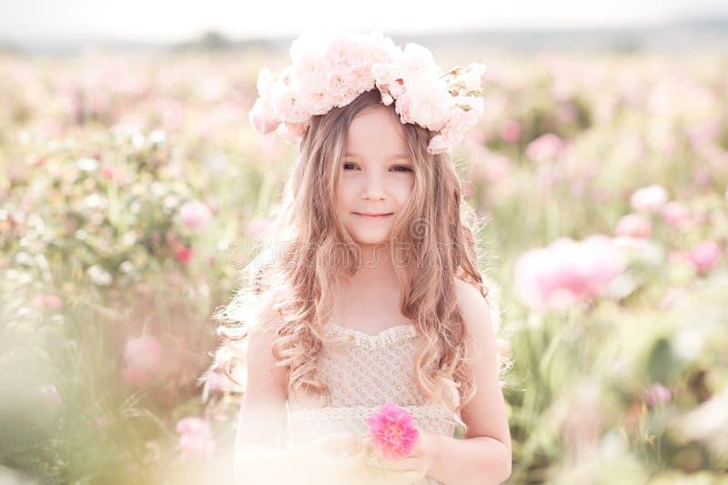Gullig barnflicka som poserar i rosträdgård royaltyfria bilder
