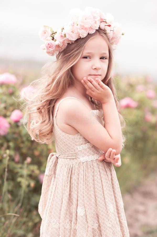 Gullig barnflicka som poserar i rosträdgård royaltyfria foton