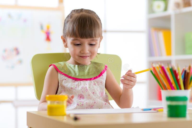 Gullig barnflicka som spenderar glatt tid genom att använda blyertspennor, medan dra i playschool arkivbilder