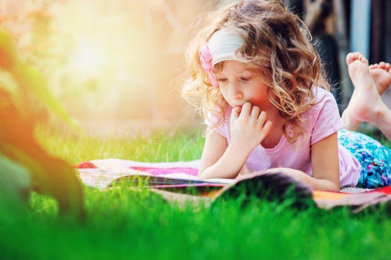 Gullig barnflickaläsebok i den utomhus- sommarträdgården arkivfoton