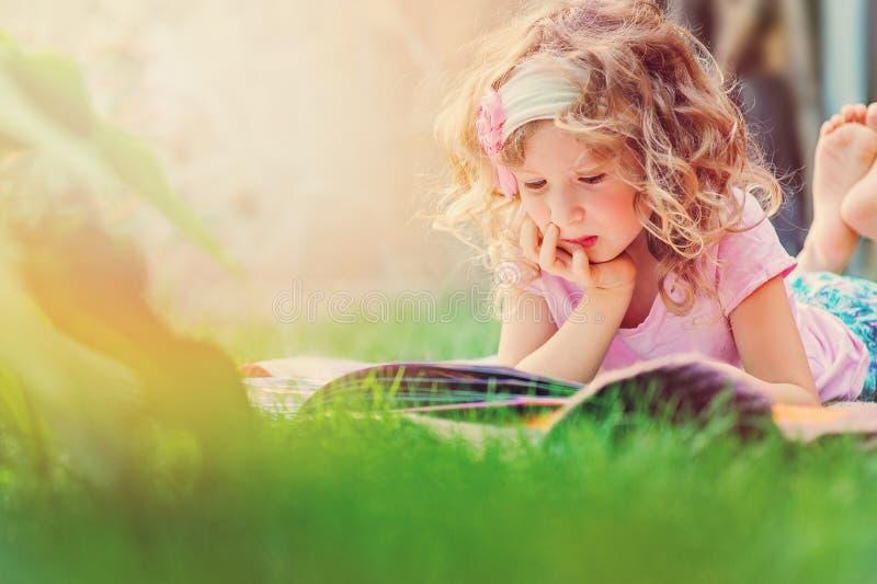 Gullig barnflickaläsebok och drömma i solig trädgård för sommar fotografering för bildbyråer
