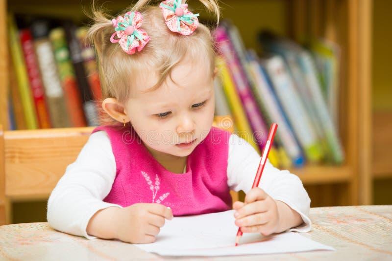 Gullig barnflickateckning med färgrika blyertspennor i förträning på tabellen i dagis royaltyfri foto