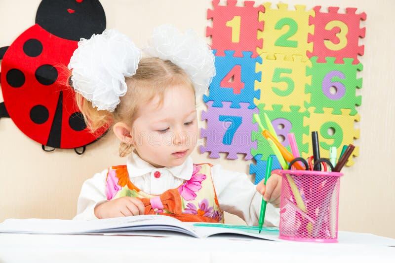 Gullig barnflickateckning med färgrika blyertspennor i förträning på tabellen i dagis fotografering för bildbyråer
