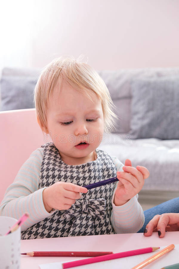 Gullig barnflickateckning med färgrika blyertspennor i förträning på tabellen i dagis royaltyfri bild