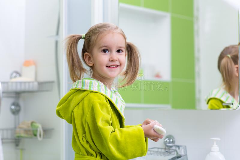 Gullig barnliten flicka med hästsvansen i den gröna badrocken som tvättar hennes händer i badrum royaltyfria bilder