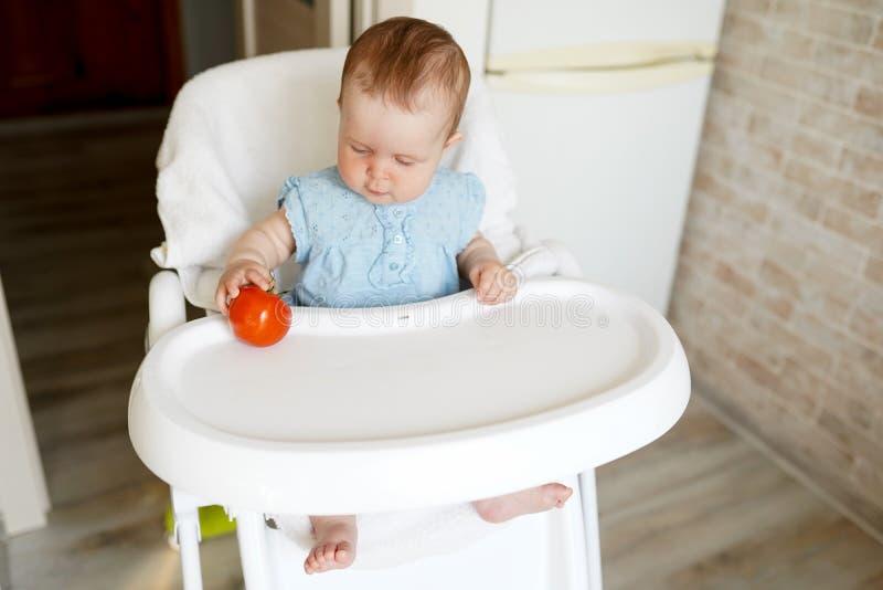 Gullig barnliten flicka som ?ter sund mat i dagis Behandla som ett barn i stol royaltyfri bild