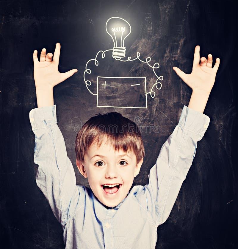 Gullig barnpojke med idékulan på svart tavla royaltyfria foton