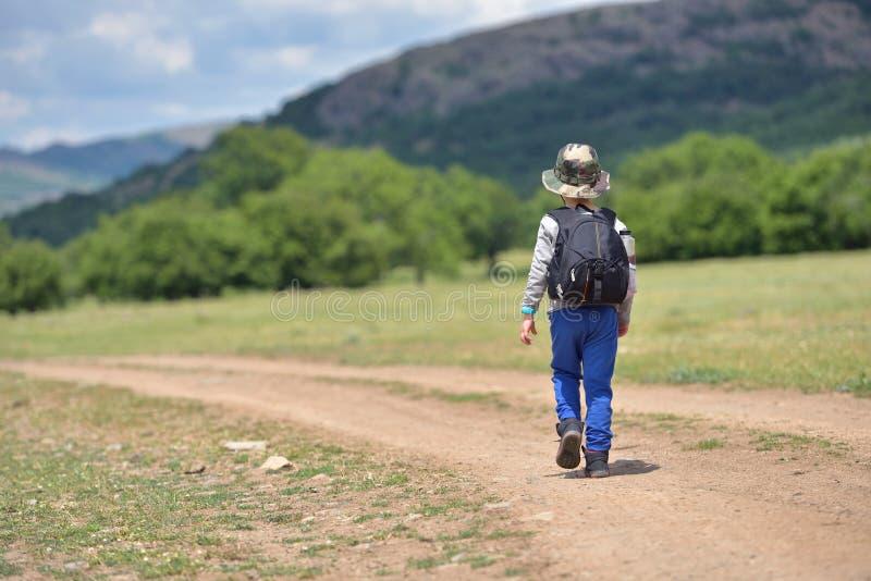 Gullig barnpojke med ryggsäcken som lite går på banan i berg Fotvandra ungen royaltyfria bilder