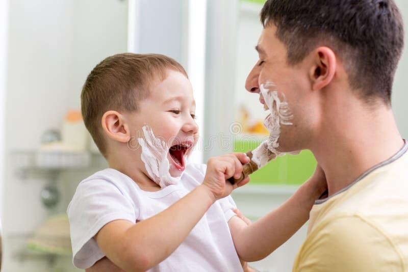 Gullig barnpojke som rakar fadern i badrum arkivbilder