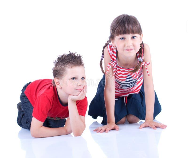 Gullig blåögd pojke och flicka som poserar i studion royaltyfri fotografi