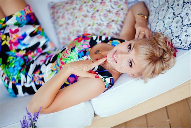 Gullig blond flicka i en ljus klänning som ligger på en vit soffa royaltyfri bild
