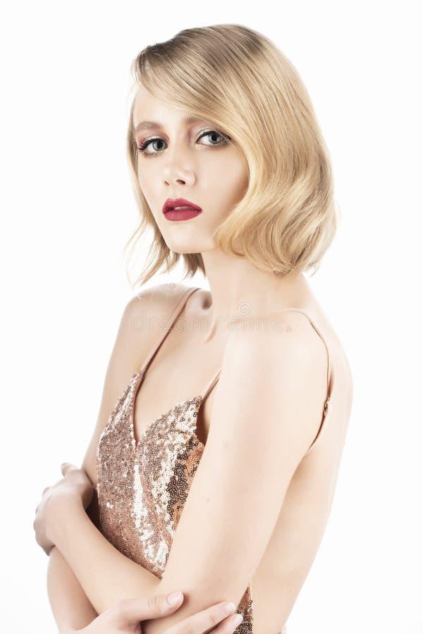 Gullig blond flicka med stora härliga ögon, röda kanter och tappningstilfrisyr som bär en guld- mousserande klänning som kramar s royaltyfri foto